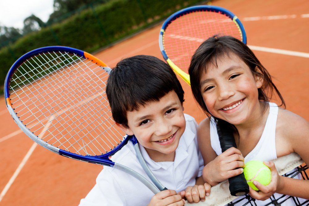 Portrait of young tennis players smiling at the court