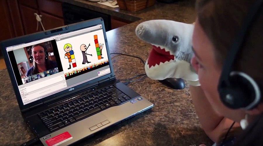 PA Virtual teacher teaching class on webcam with shark puppet