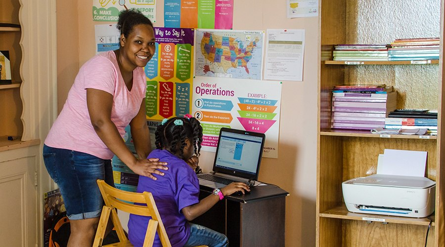 Mother assisting daughter complete school work on her laptop
