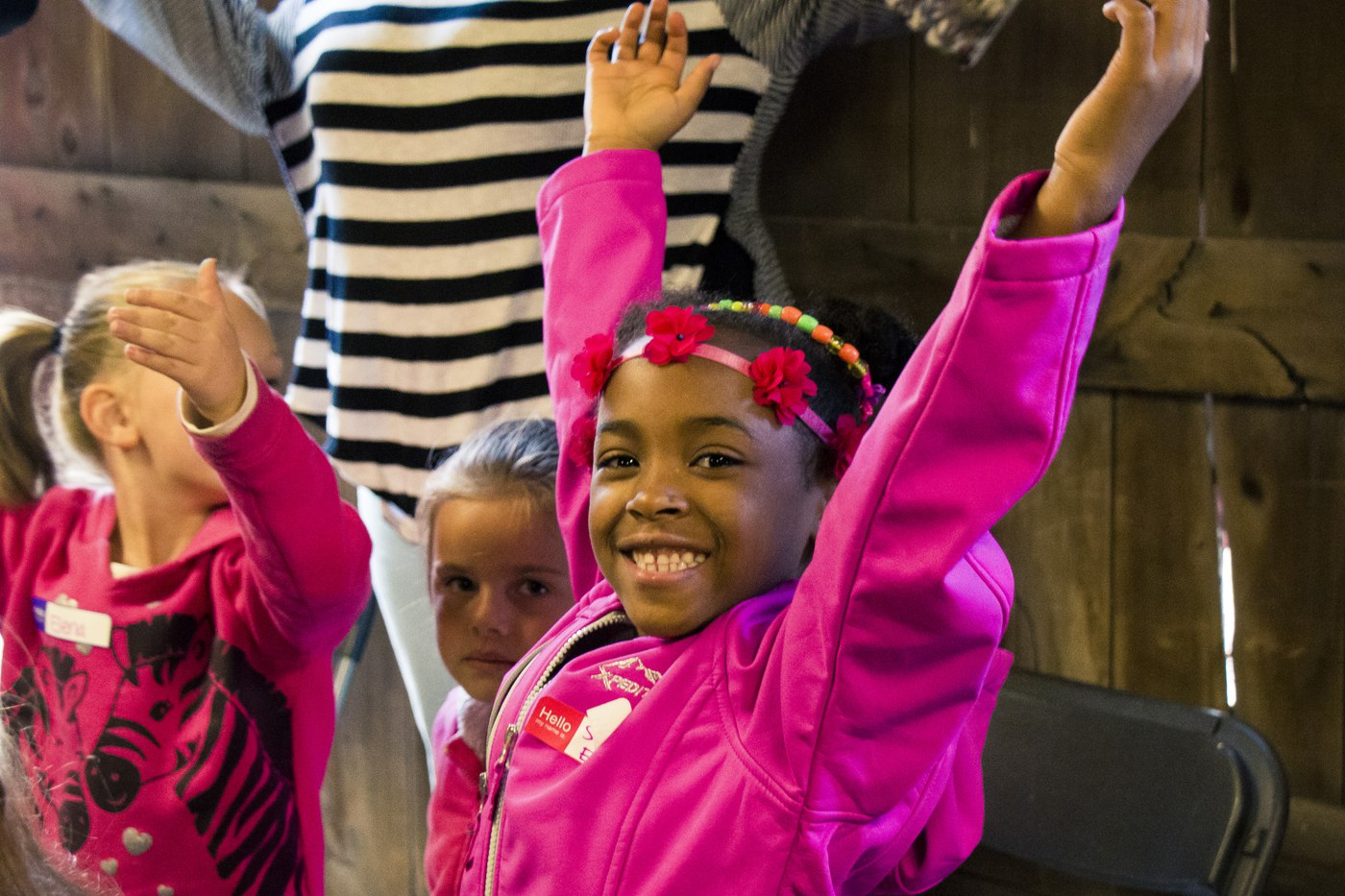 Excited kindergarten student with arms raised