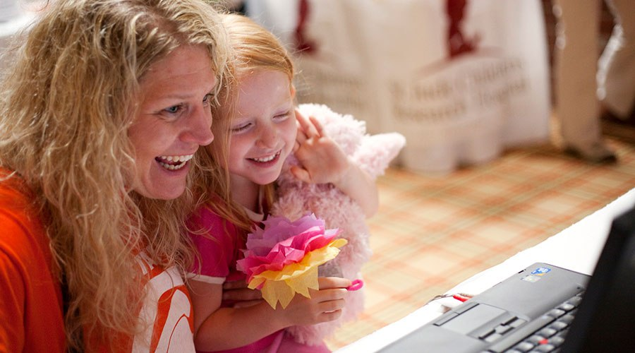 PA Virtual parent looking at laptop screen with daughter